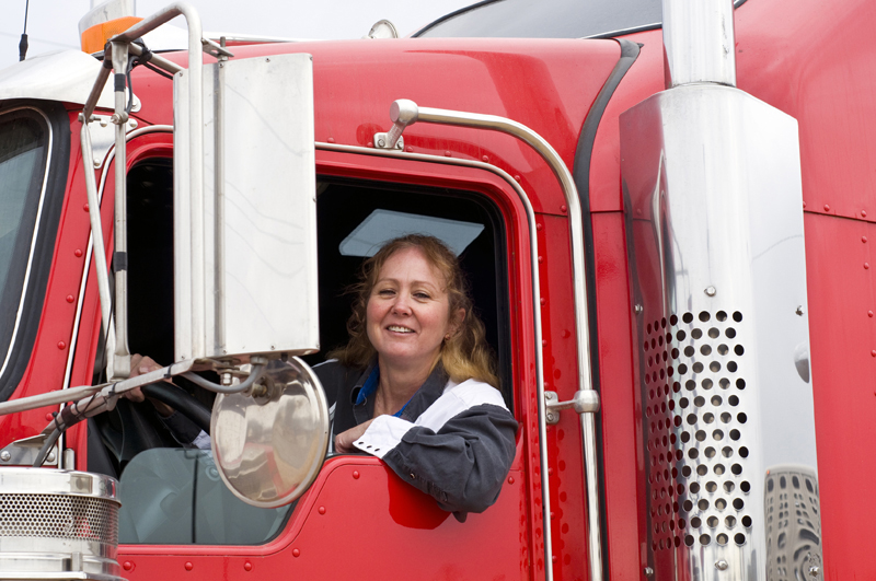 photo of a caucasian female truck driver sitting in the driver seat of her red semi truck, smiling towards the camera.