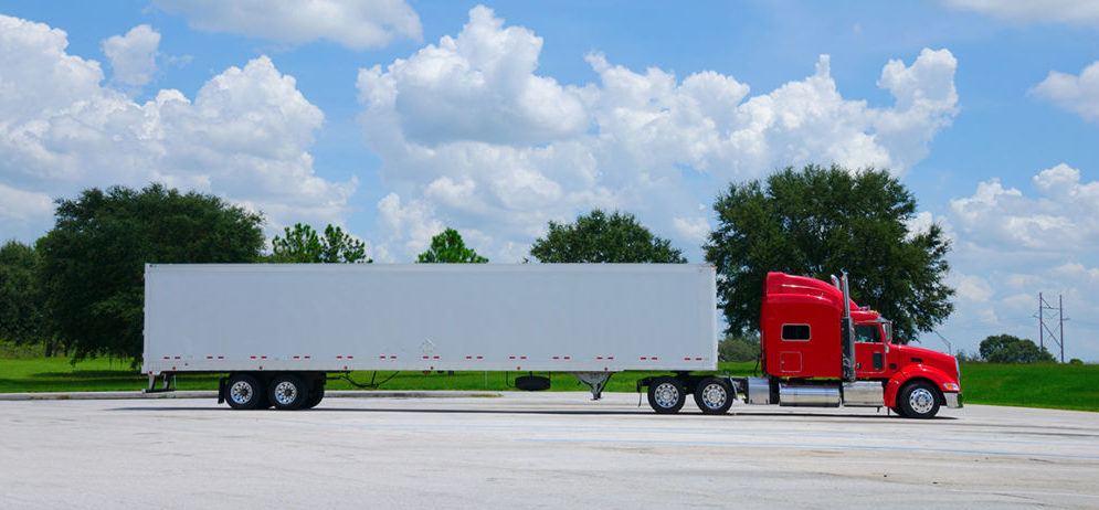 photo of a red semi tractor truck with a clean white cargo container trailer against a simple colorful background of trees and blue sky