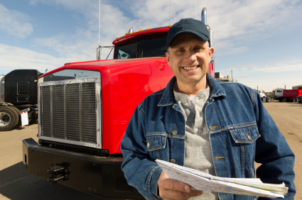 image of a caucasian male truck driver standing in front of a shiny red tractor against a blue sky with whispy clouds
