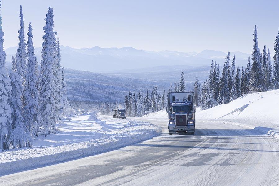 semi-truck driving on a snowy road